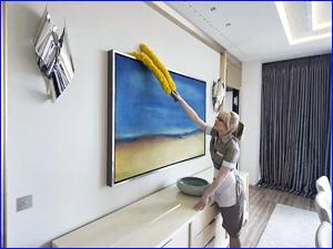Сотрудник клининговой компании вытирает пыль в квартире