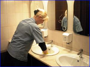 Сотрудник клининговой компании убирает туалет в ресторане и кафе