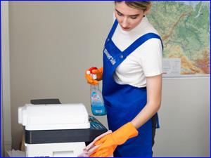 Клинер протирает пыль на офисной технике в кабинете